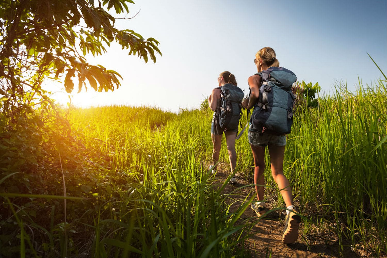 Two girls hiking with internal and external frame backpacks