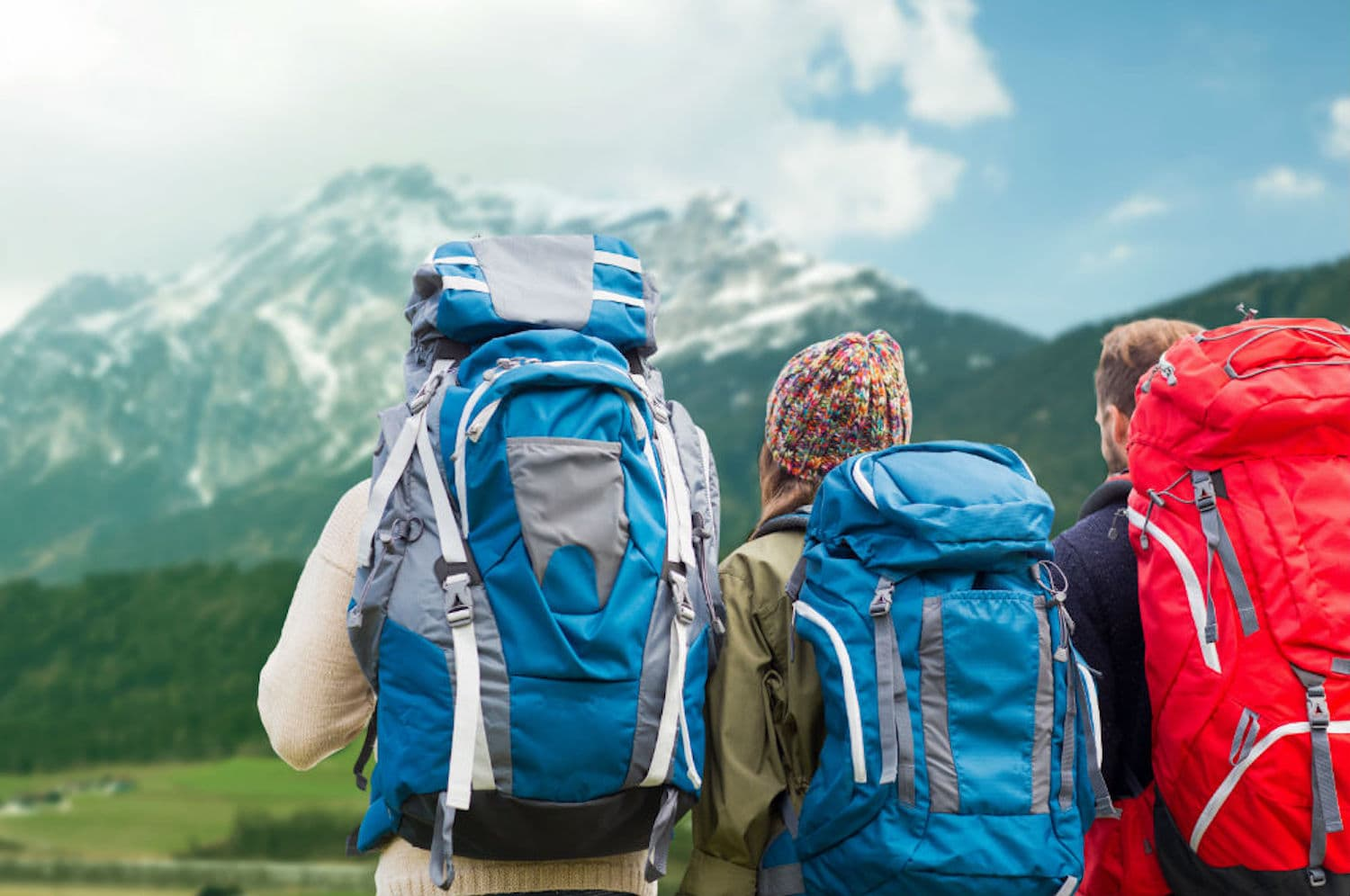 Three persons are standing with the backpacks and looking over to the mountain