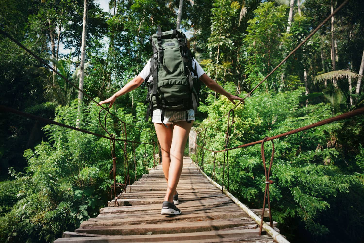 A woman going over the bridge with the backpack