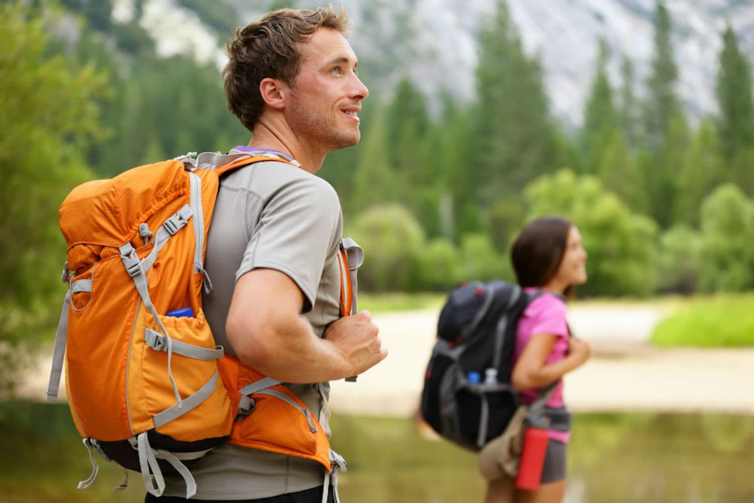 A man and a woman standing with the hiking backpacks