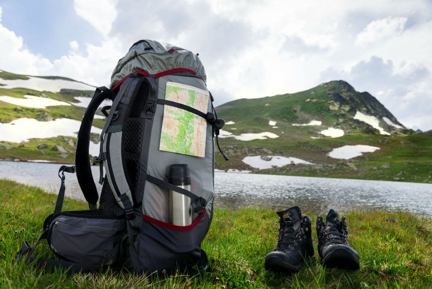 Backpack and hiking shoes next to the lake and mountains