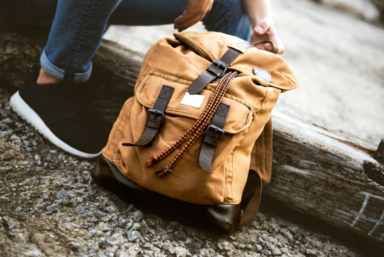 A person holding brown backpack