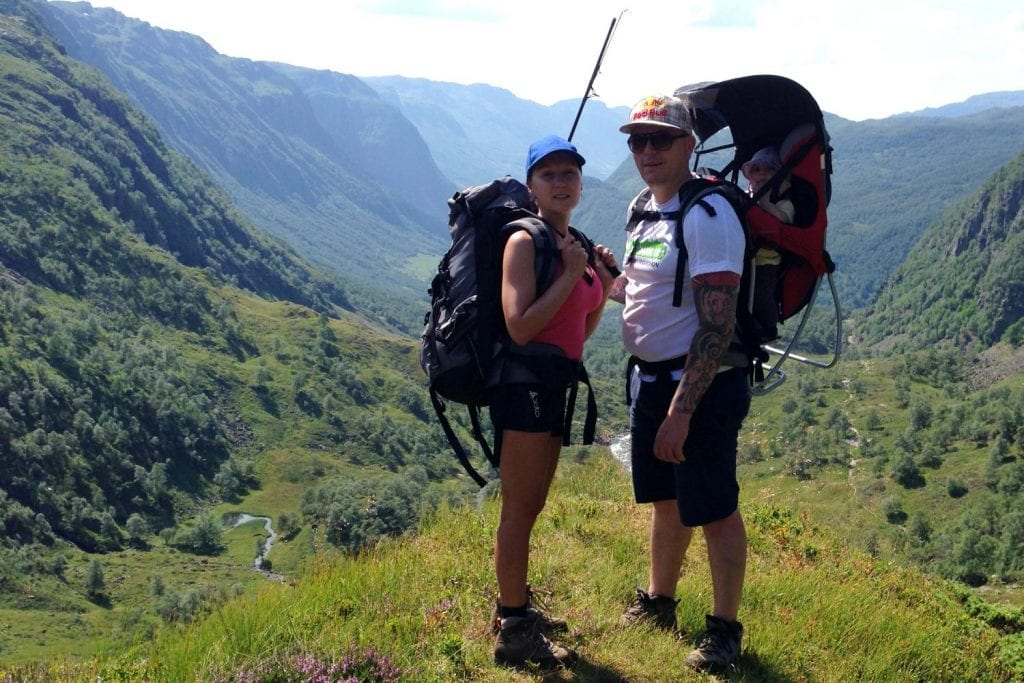 Julija and Thomas from Leisure Hiking standing with in their baby in the baby carrier, and hiking backpack in the Norwegian mountains of Blomstolen