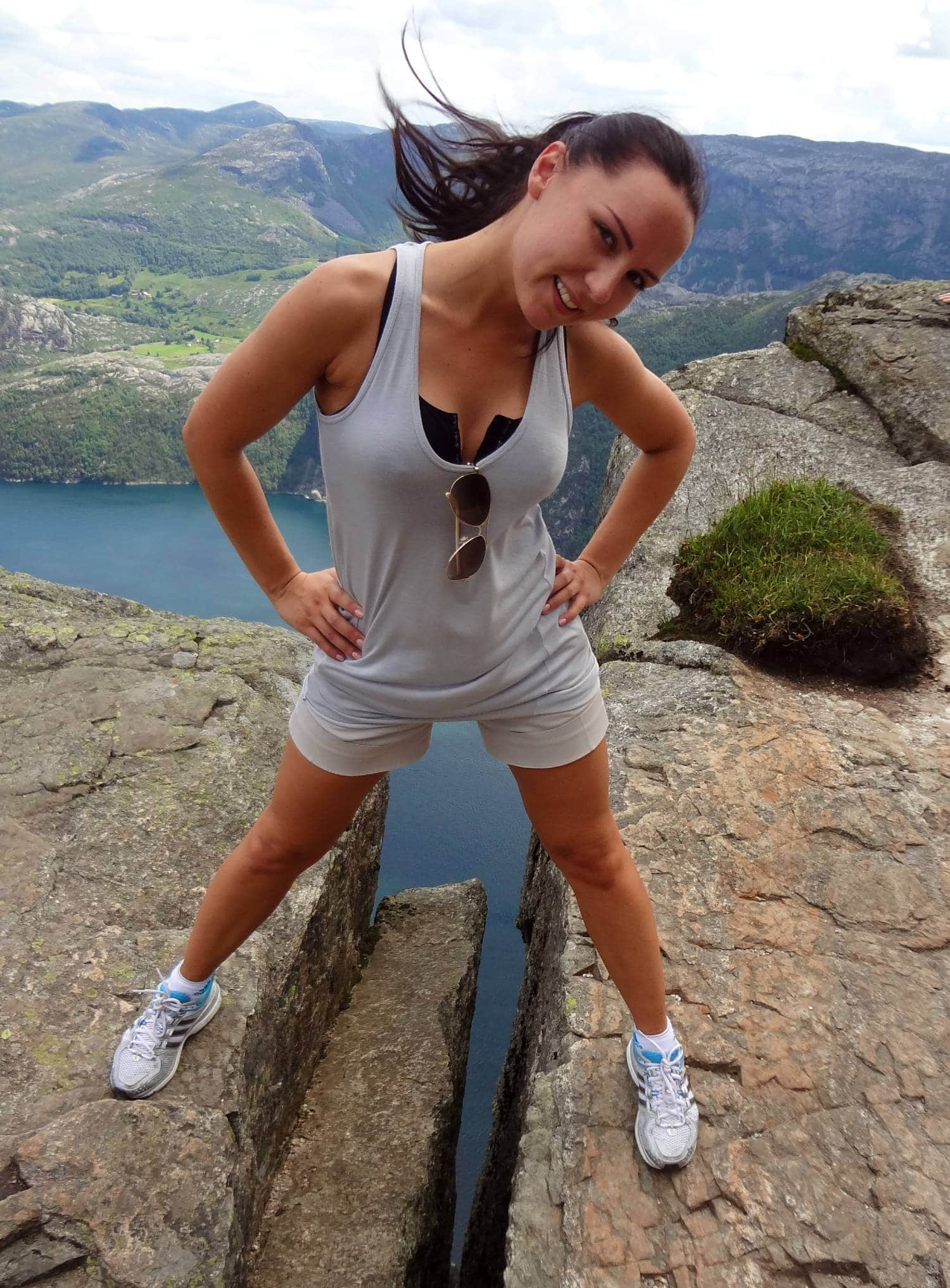 Julija from Leisure Hiking standing between two mountain formations and a 800 meter drop down to the fjord.