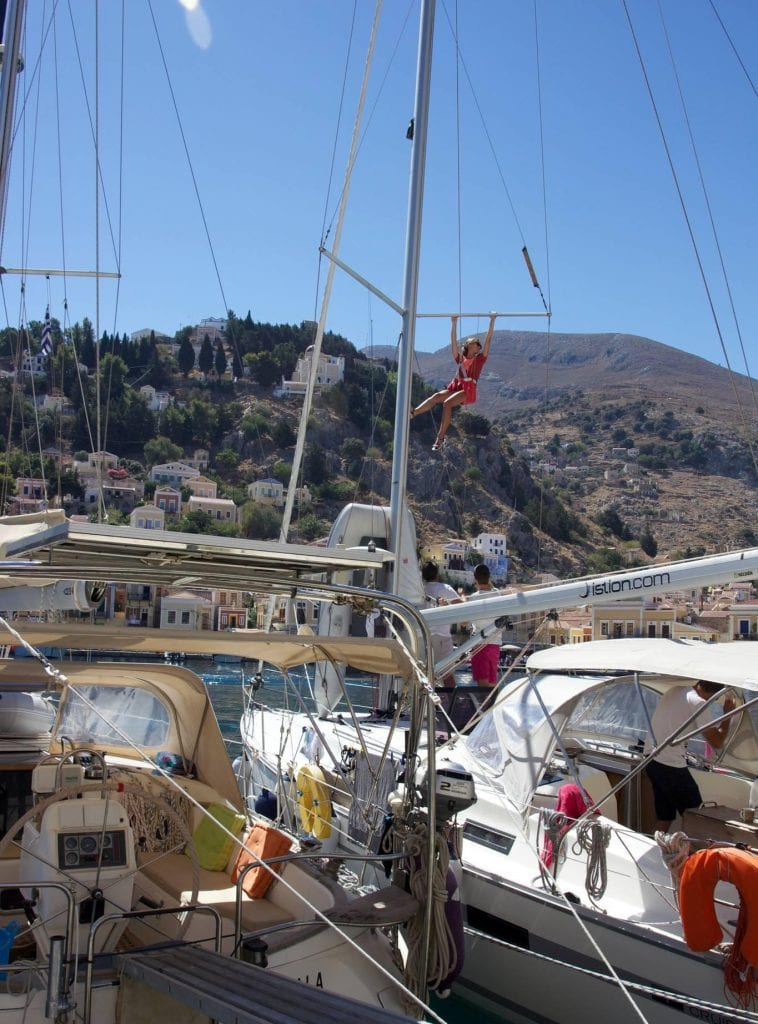 Sigita of Leisure Hiking is hanging from the mast of a sailboat in Greece on one of her adventures to the Greek islands.