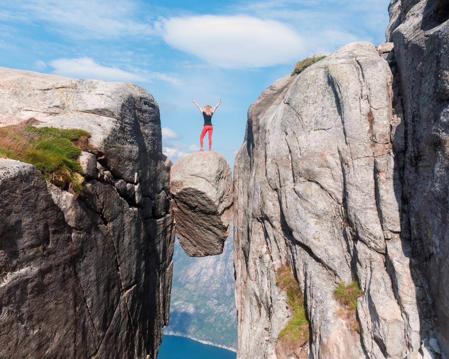 Girl standing on the kjeragbolten rock stuck between two mountains with the fjord below