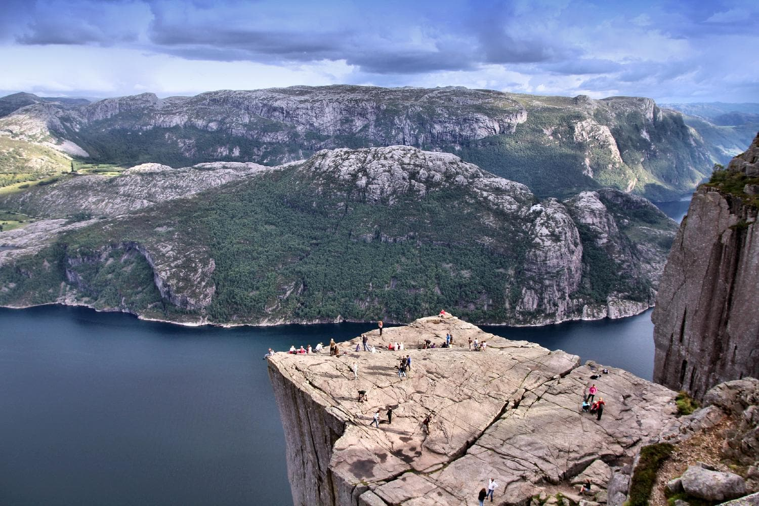 The Pulpit Rock - Preikestolen - from above with people on the rock looking down to Lysefjorden