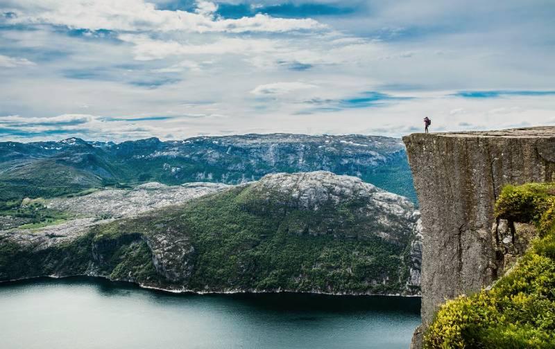 Hiker overlooking Lysefjorden from the endge of Preikestolen mountain in Norway.