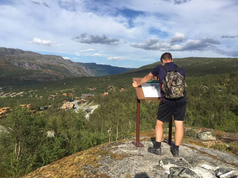 Hiker looking at info sign while hiking in Norway