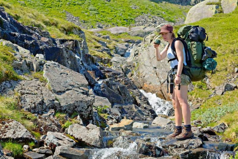 A female hiker having a break by a tiny river to drink fresh mountain water