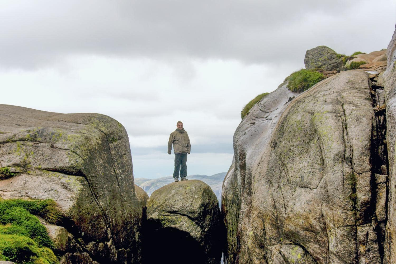A hiker standing on top of the Kjeragbolten stone between two mountains in Lysefjorden Norway