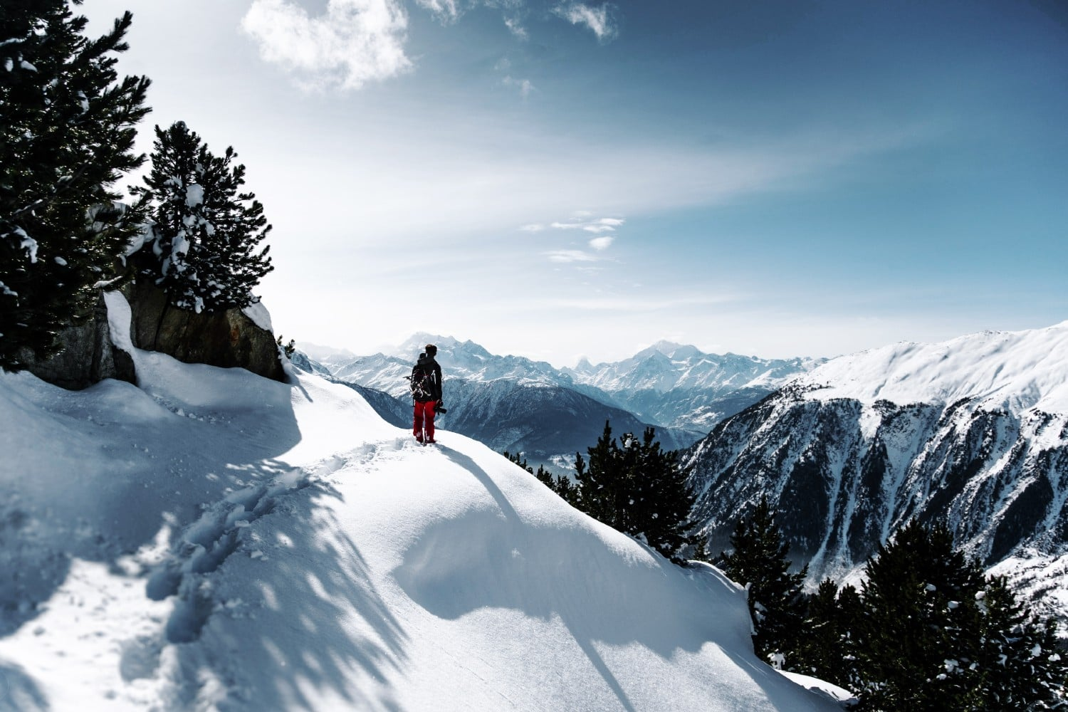 A winter hiker standing on mountain top looking out over winter covered valley