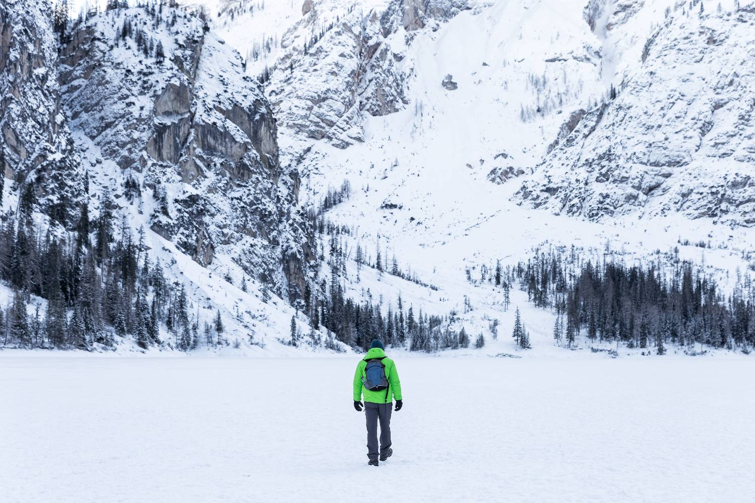 Man hiking in winter towards snow covered mountains.