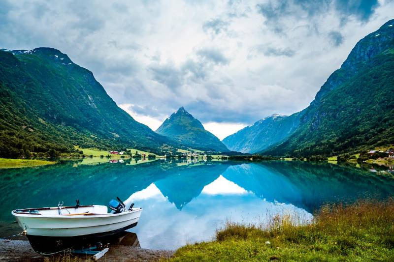 Fjord landscape with majestic mountains in Norway with reflecting sea and a white boat at shore.