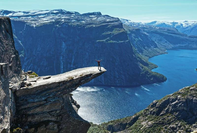 A man standing on the tip of the Trolltunga mountain