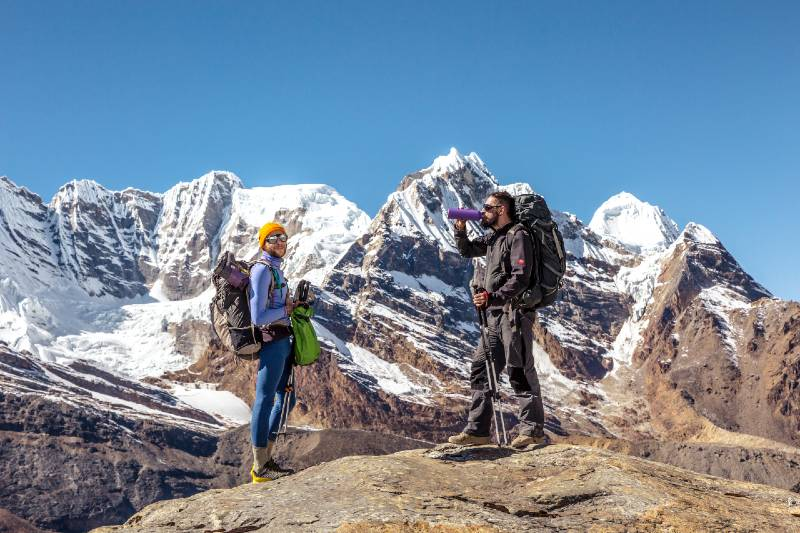Two hikers standing. One of them drinking water.