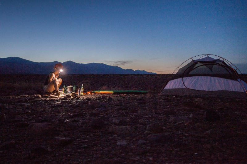a girl sitting next to the tent with the headlight