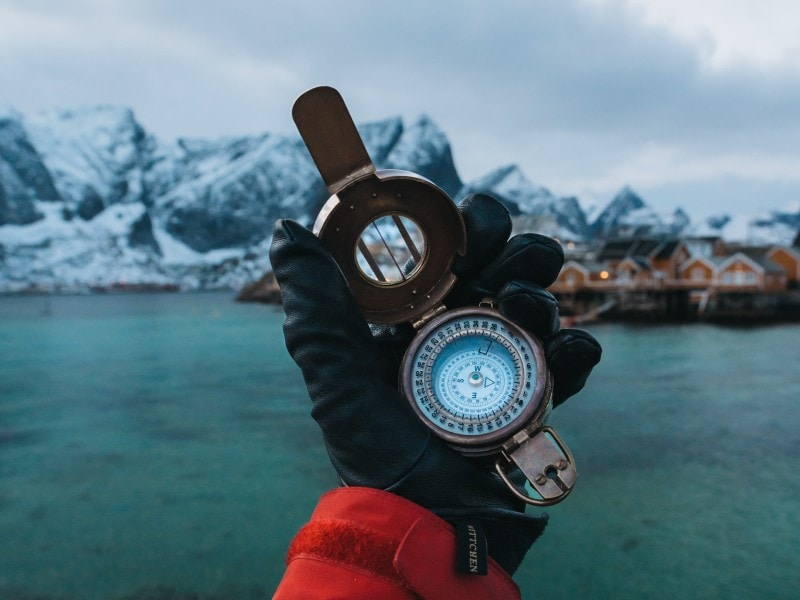 a man's hand with the glove on and a compass