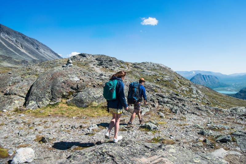 Two hikers are hiking in the mountains